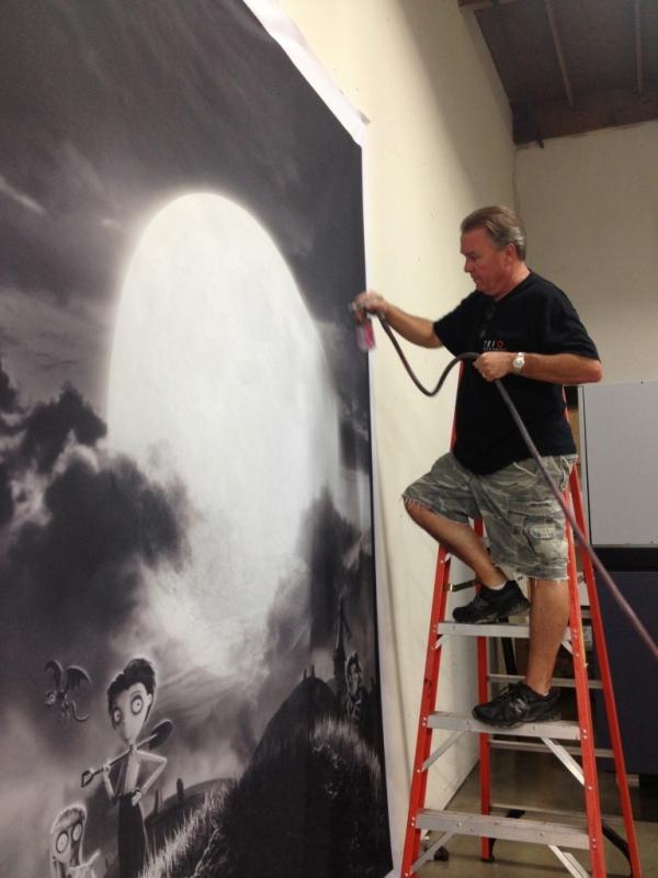 TRIO owner, Ed Strang, airbrush painting Frankenweenie backdrop